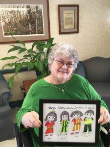 Jackie holds up her artwork